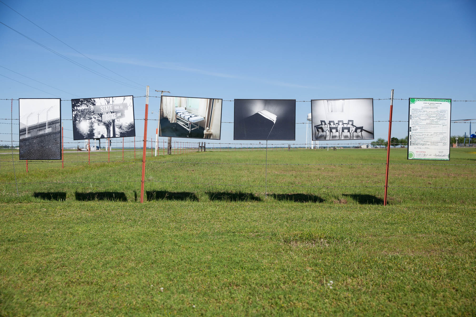 Scott Langley's death penalty photography exhibit, hanging on barbed wire fencing outside the Arkansas execution facilities.